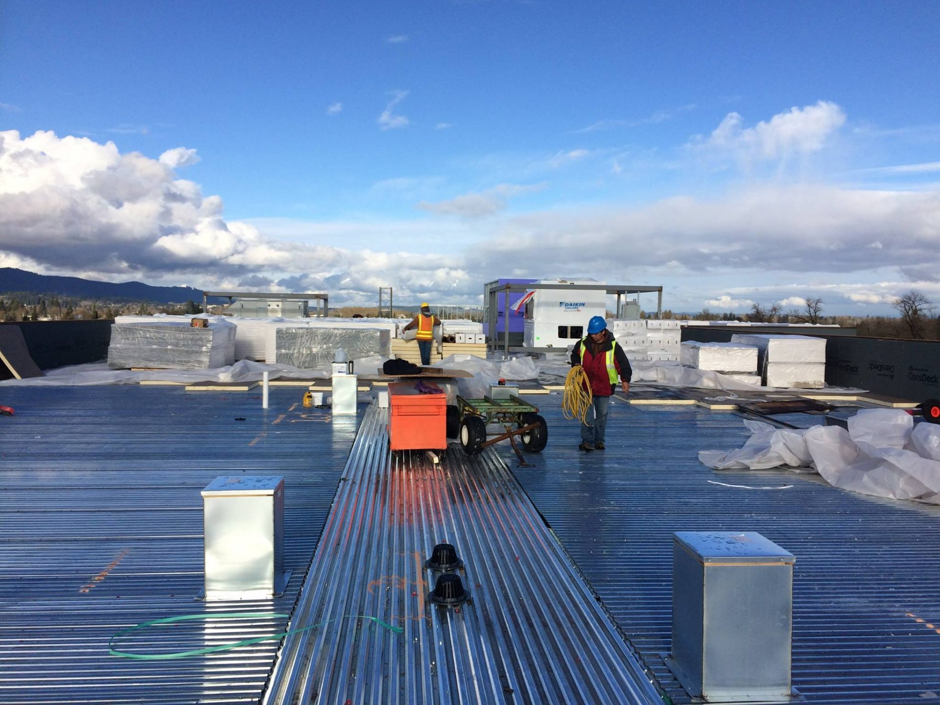Guys working on a commercial roof. About roof restoration