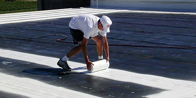 One of our commercial roofers rolling white fabric on a roof.